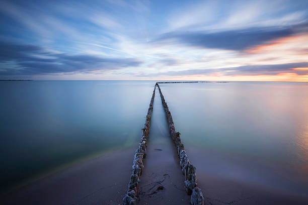 seascape with breakwaters at sunset - infinity stock photos and pictures