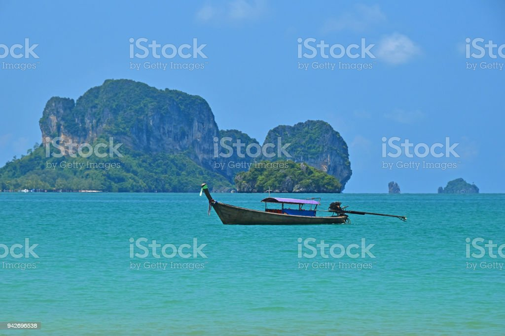 Tranquil seascape of tropical island, long tail boat, turquoise blue...