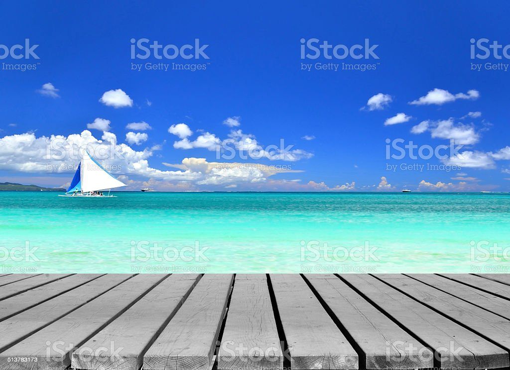 Seascape with sailboat and wooden pier stock photo