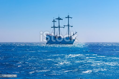 Seascape with sailing ship at sunny day. Blue sailing vessel floating in the sea. Copy space. The concept of calmness, silence and unity with nature.