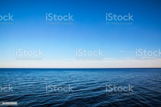Seascape with sea horizon and almost clear deep blue sky - Background
