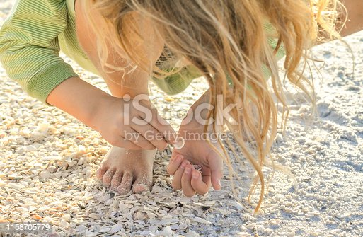 Collecting shells on the beach in Florida, little girls bends over to choose the best shells. Close up