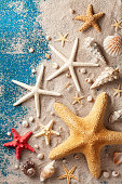 Seashell, starfish and beach sand on blue wooden background. Summer holiday and vacation travel concept. Top view and vertical.