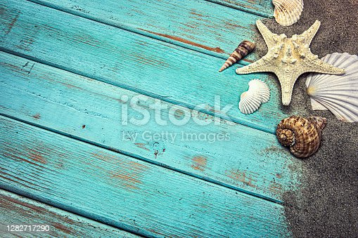 istock Seashells in the Sand on blue wood background 1282717290