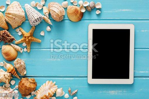 istock Seashells on blue wood, booking tickets on digital tablet 817420220