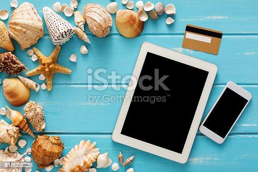 istock Seashells on blue wood, booking tickets on digital tablet 818688236