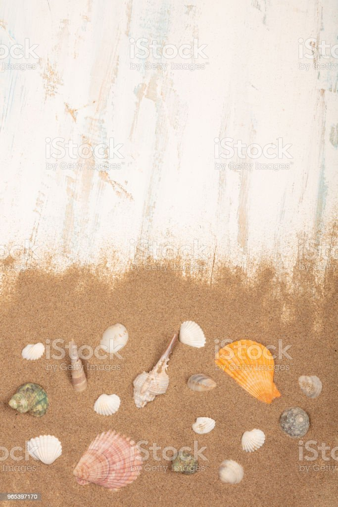 Seashells with sand on a wooden background royalty-free stock photo