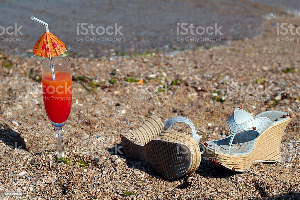 Seashore cocktail and shoes on the beach royalty-free stock photo