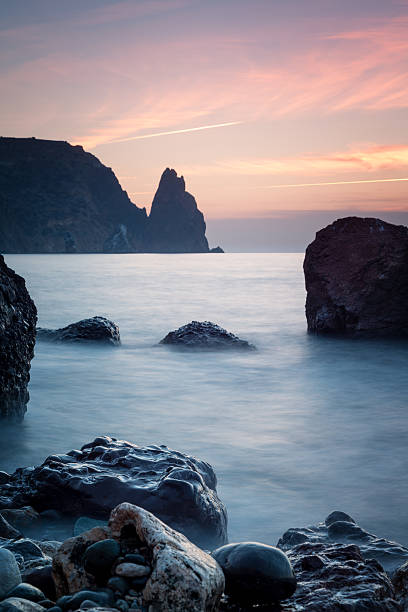 Seashore with misty water at sunset stock photo