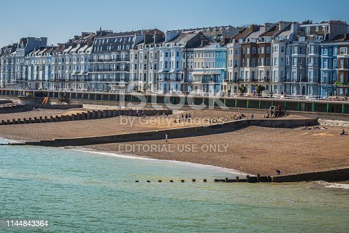 Seaside at Hastings in the UK.  Victorian row houses line the streets with the promenade and beach in the ​foreground. Unrecognizable people on the beach.