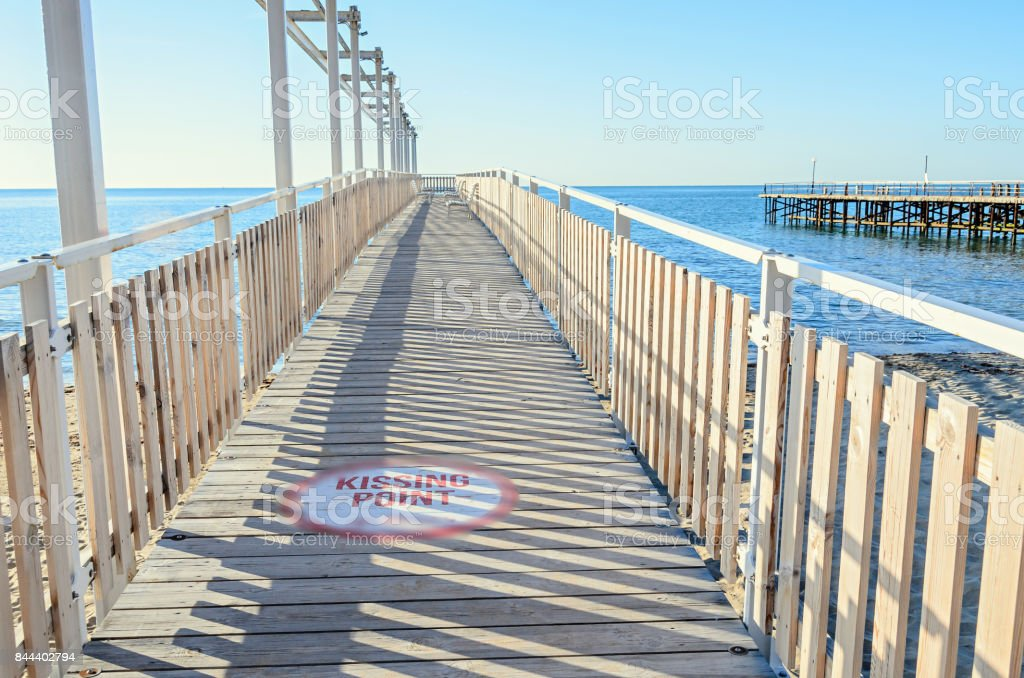 Seaside bridge with kissing points and benches on Black Sea, blue clear water and sunny day sky stock photo