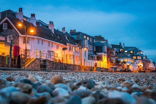 Seaside cottages overlooking pebble beach illuminated Lyme Regis Devon UK