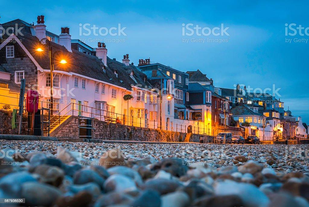 Seaside cottages overlooking pebble beach illuminated Lyme Regis Devon UK stock photo