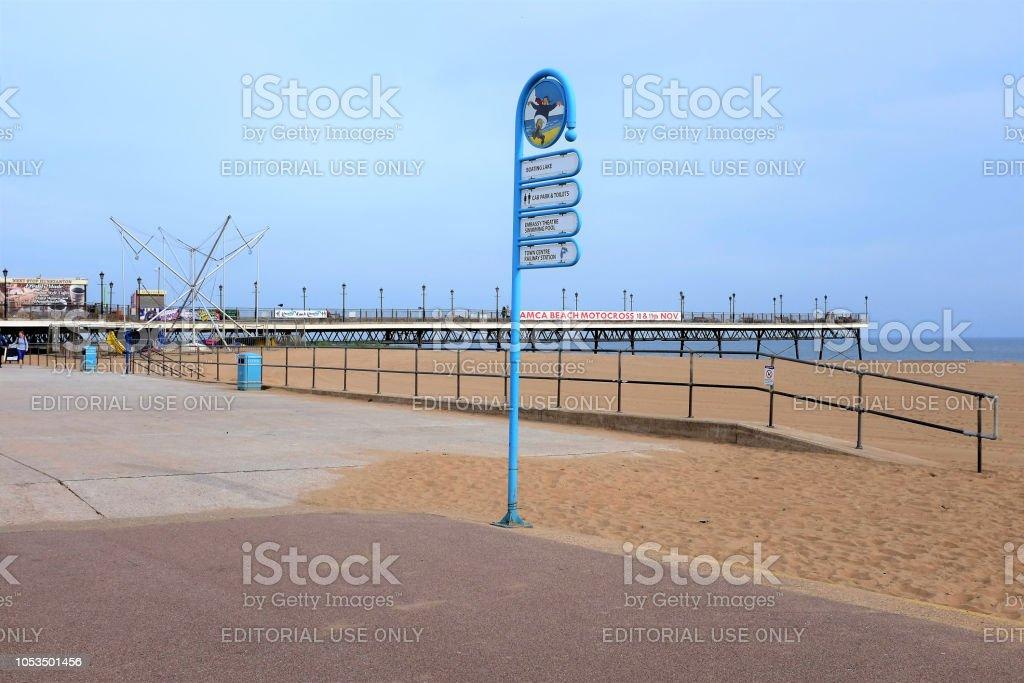 Am Meer-Wegweiser und Pier. – Foto