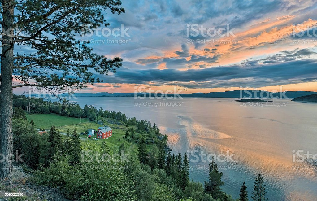 Seaside Farm house in Northern Norway with majestic cloudscape stock photo