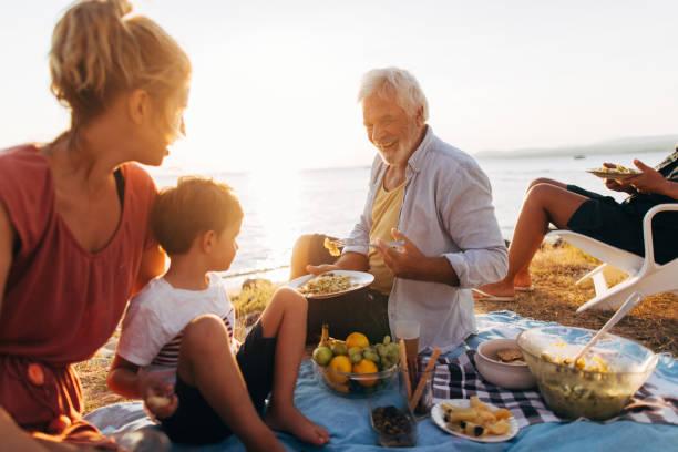 seaside picknick mit familie - griechische partyspeisen stock-fotos und bilder