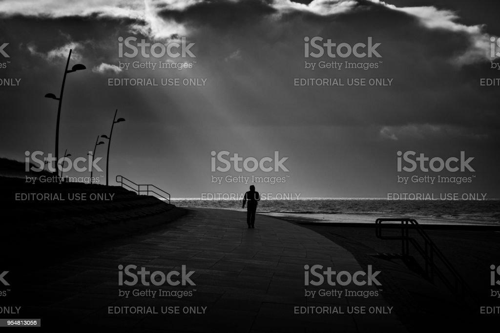 Seaside promenade on eastfrisian island Borkum Borkum, Germany - 02/11/2018: A man walks solely along the seafront of eastfrisian island Borkum in the late afternoon under a dramatic sky. Adult Stock Photo