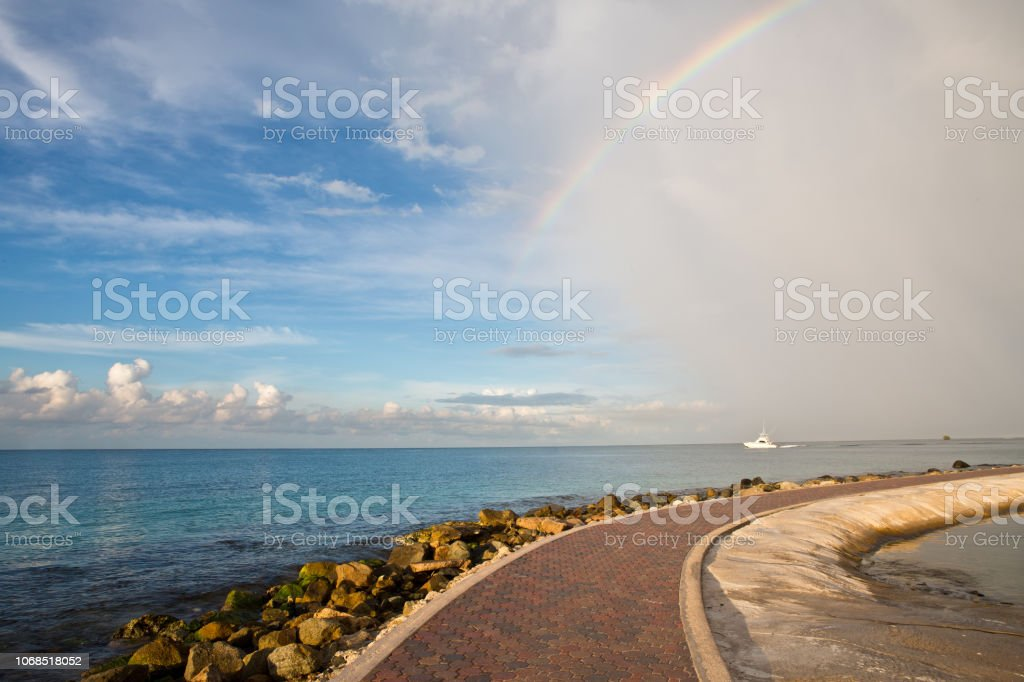 Seaside promenade with rainbow in Oranjestad Aruba stock photo