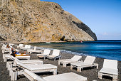 Perissa, Santorinii Island, Greece-May 12, 2018- A young couple relaxes on comfortable lounge chairs on the black sand beach of Perissa, Greece