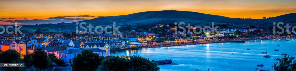 Seaside resort town ocean bay illuminated at sunset Swanage Dorset stock photo