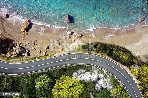 Winding coastal road approaching a beautiful beach with sea waves and turquoise water. Golden sands and rocks for a perfect summer destination. Aerial view.