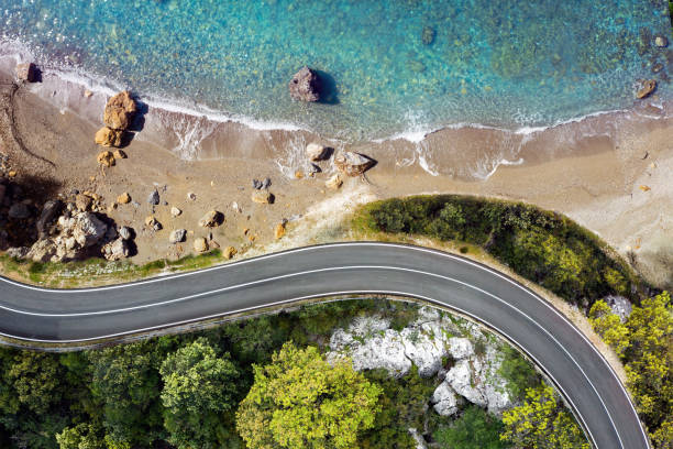Seaside road approaching a beach, seen from above Winding coastal road approaching a beautiful beach with sea waves and turquoise water. Golden sands and rocks for a perfect summer destination. Aerial view. road trip stock pictures, royalty-free photos & images