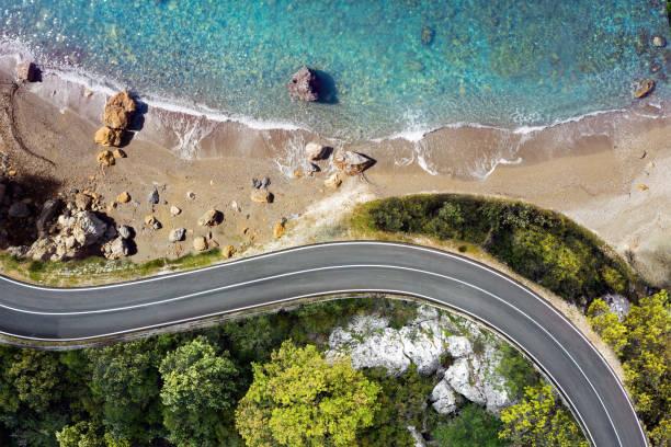 sahil yolu yukarıdan görülen bir plaja yaklaşıyor - araba yolculuğu stok fotoğraflar ve resimler