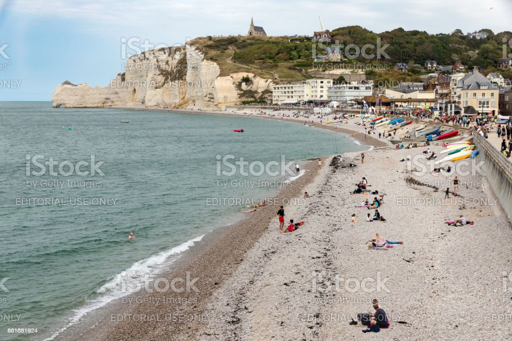 Seaside visitors and fishing boats at beach Etretat, Normandie, France stock photo