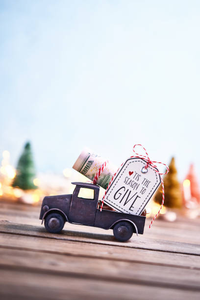 season to give. truck carrying roll of dollars with holiday background - gift tag note stock photos and pictures
