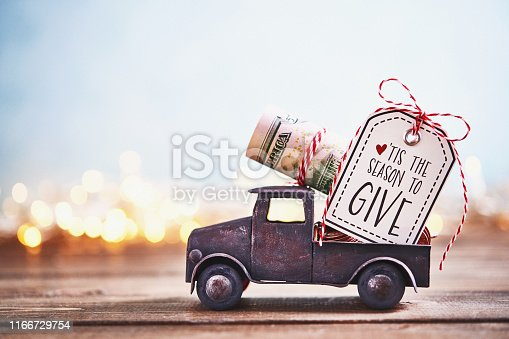 istock Season to Give. Truck carrying roll of dollars with holiday background 1166729754