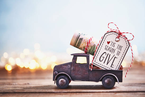 season to give. truck carrying roll of dollars with holiday background - charity and relief work stock pictures, royalty-free photos & images
