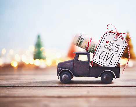Season to Give. Truck carrying roll of dollars with holiday background