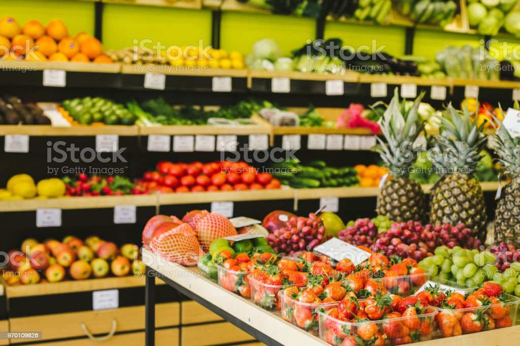 Seasonal and exotic fruits and vegetables on the food shelf in the...