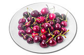 Seasonal fruit: aromatic sweet ripe cherry in plate isolated on white background. Studio Photo