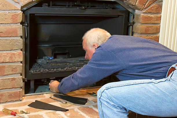 Seasonal Maintenance on Gas Fireplace stock photo
