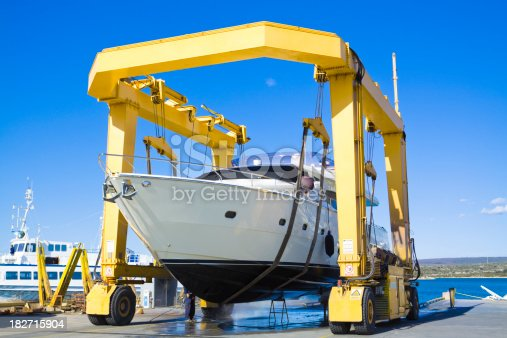large luxury motor yacht hanging from a shipyard craneCHECK OTHER SIMILAR IMAGES IN MY PORTFOLIO....