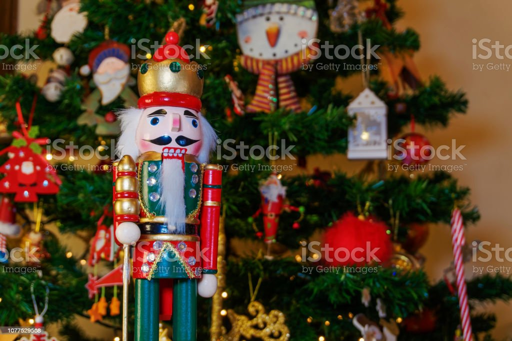 Seasonal toy figure before an illuminated artificial Christmas tree with lights and colorful decorations. stock photo