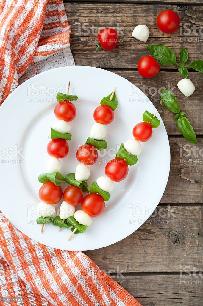 Seasonal traditional Italian caprese salad skewers with tomatoes basil and stock photo