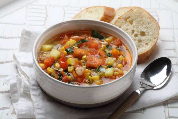 Seasonal vegetable soup with potatoes, carrots, onions, garlic, white beans, corn, tomatoes and parsley Seasonal vegetable soup with potatoes, carrots, onions, garlic, white beans, corn, tomatoes and parsley vegetable soup stock pictures, royalty-free photos & images