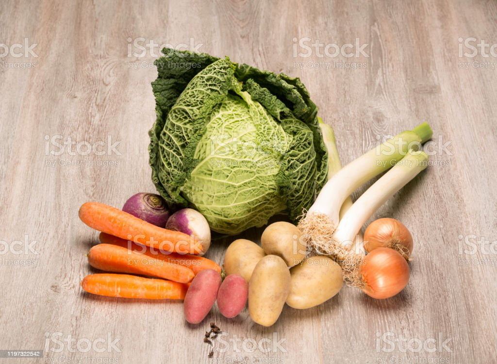 """Seasonal vegetables for the preparation of the French """"pot au feu"""" Seasonal vegetables for the preparation of the French """"pot au feu"""" assortment of vegetables to cook a pot au feu, French culinary specialty there is a cabbage, carrots, turnip, potato, onion, leek, clove Autumn Stock Photo"""