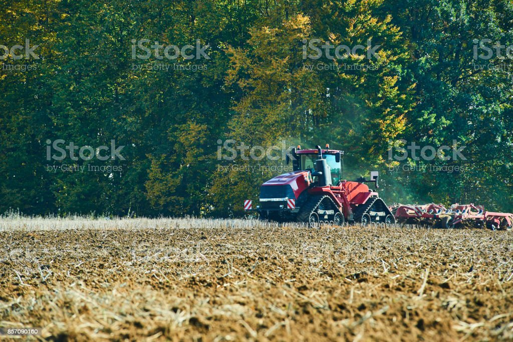 Seasonal work in a agricultural landscape. Tractor plowing the field. stock photo