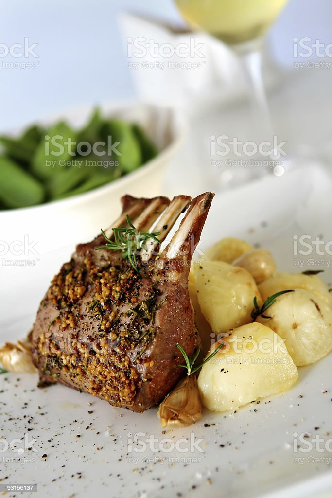 Seasoned rack of lamb served with a side dish stock photo