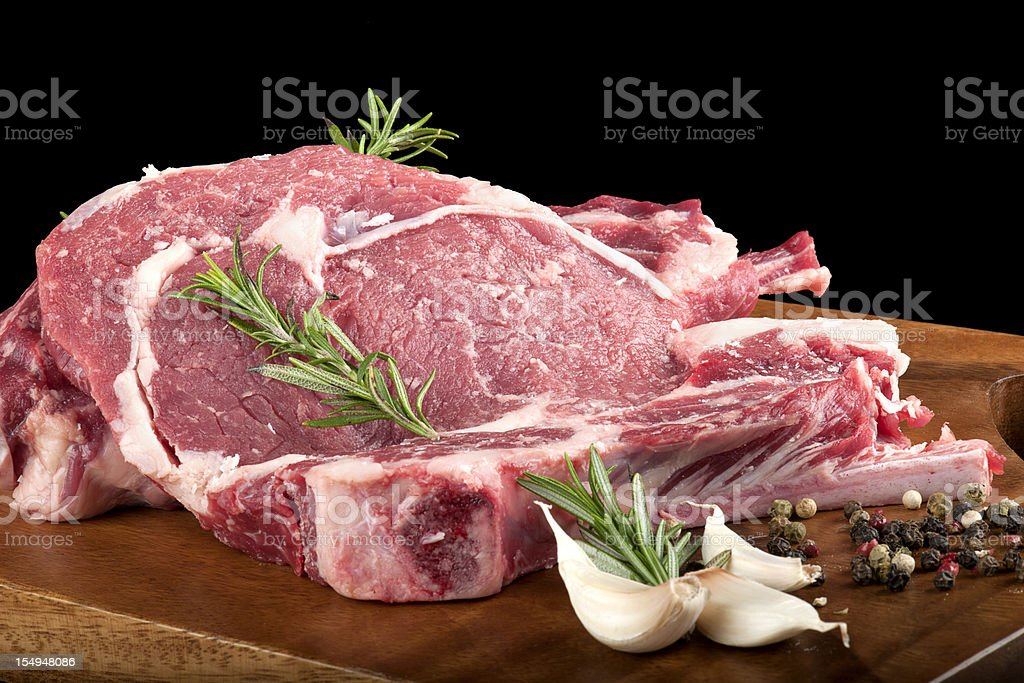 Seasoned raw red meat on a wooden cutting board stock photo