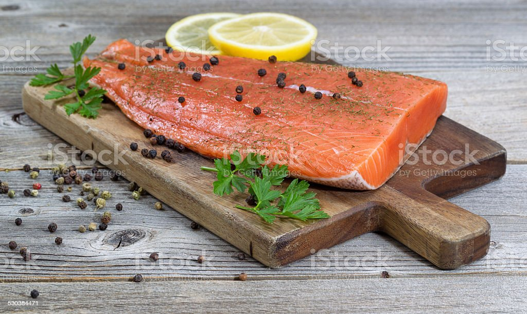Seasoned Salmon Fillet on rustic wood stock photo