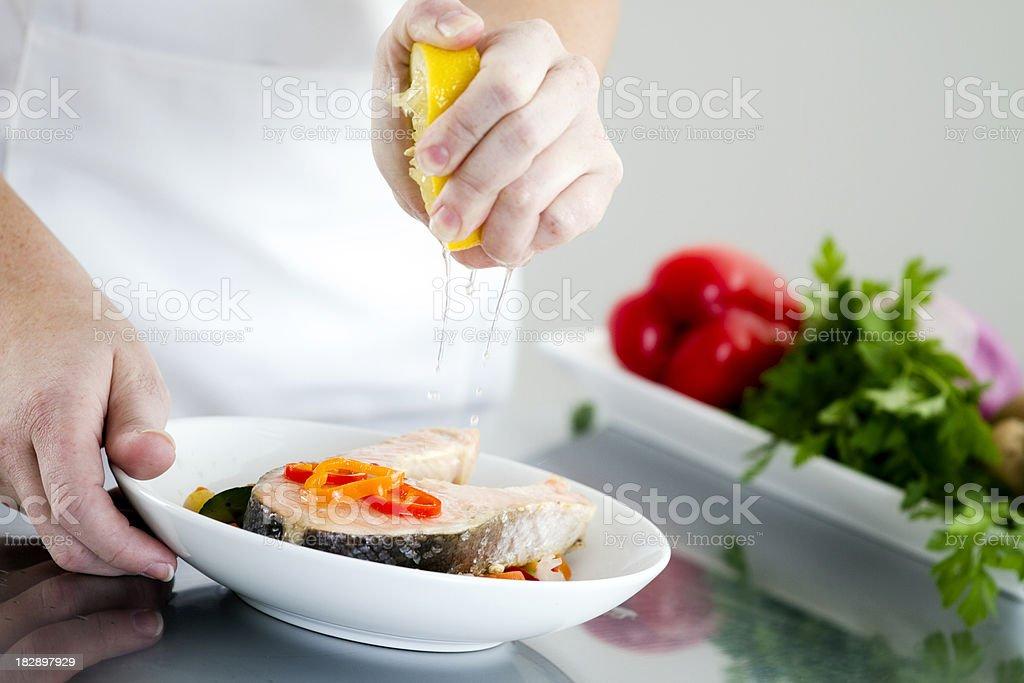 Seasoning a Salmon Dish royalty-free stock photo