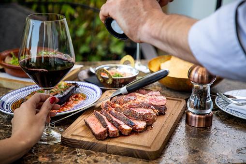Seasoning juicy medium rare beef steak with salt grinder, cut on wooden board on restaurant table