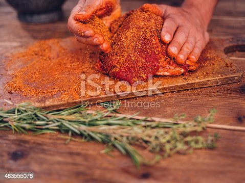 Low angle shot of some spicy seasoning being rubbed into a piece of raw pork on a wooden surface with herbs in the foreground