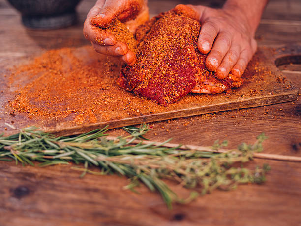 Seasoning of herbs and spices being rubbed into pork Low angle shot of some spicy seasoning being rubbed into a piece of raw pork on a wooden surface with herbs in the foreground rubbing stock pictures, royalty-free photos & images