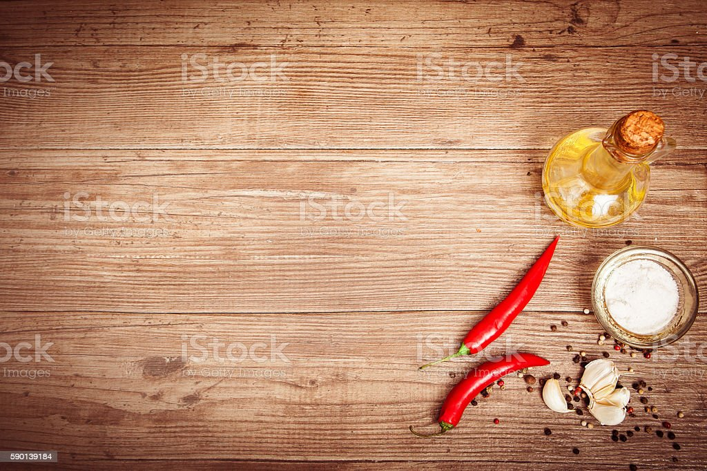 Seasoning, olive oil, chili peppers, garlic on dark wooden backg stock photo