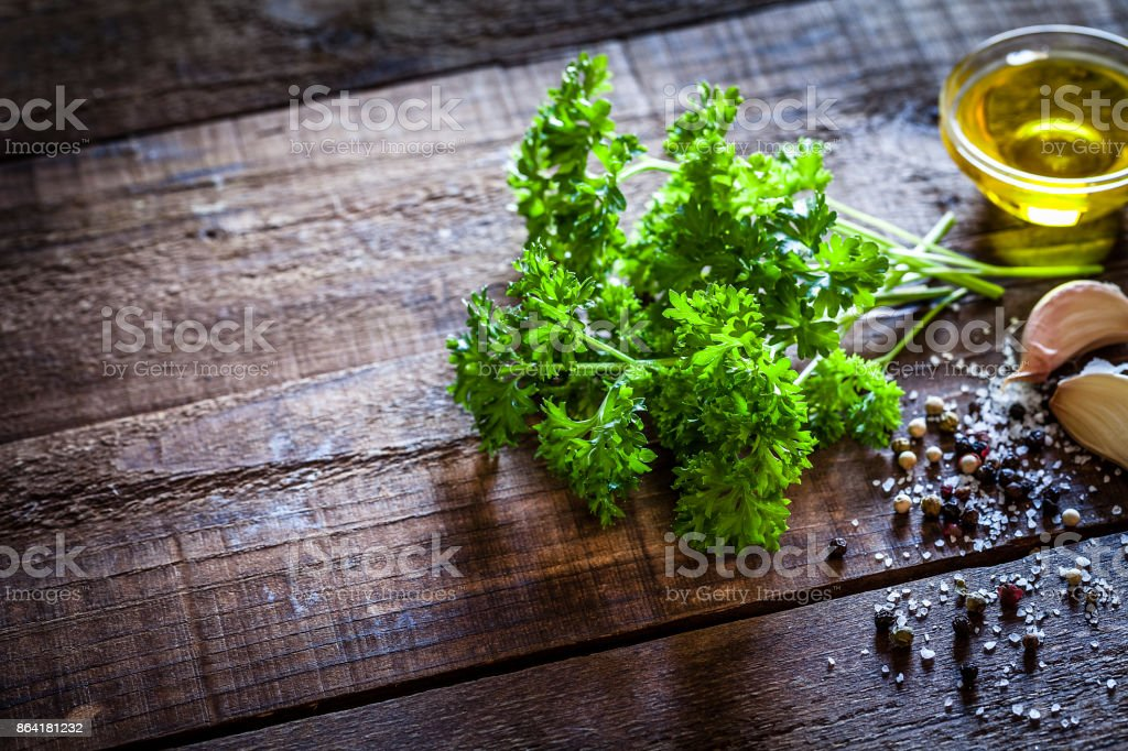 Seasoning: parsley bunch on rustic wooden table royalty-free stock photo